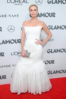 """Zum Niederknien - Charlize hat sich gemäß des Abends, der Verleihung des""""Glamour Women of the Year""""-Award, im schneeweißen Powerlook gekleidet. Das trägerlose Korsagenkleid von Givenchy ist edgy, klar aber durch die Einarbeitung von weißen Federn am Bein auch feminin verspielt. Ihre kurze blonde Pixie-Frisur ist in einem strengen Seitenscheitel zurückgekämmt."""