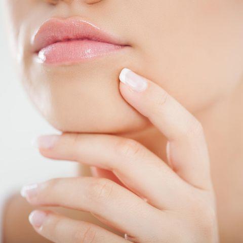 Fassen Sie sich häufig ins Gesicht, kann das eine Ursache für Pickel am Kinn sein.