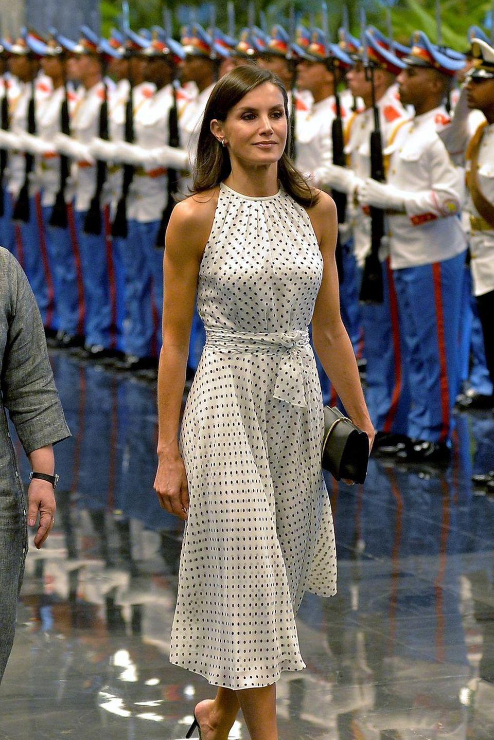 Denn die spanische Königin trägt ihr hübsches Punktekleid mit Neckholder-Ausschnitt und Taillengürtel bereits zum dritten Mal. Einzig und allein ihre Pumps, als auch ihre Ohrringe variiert die 47-Jährige. Für den offiziellen Besuchdes in Kuba, entscheidet sich Letizia für schlichte Gold-Ohrringe des Labels Coolook, schwarze Pumps von Steve Madden und eine ebenfalls schwarze Clutch von Nina Ricci.