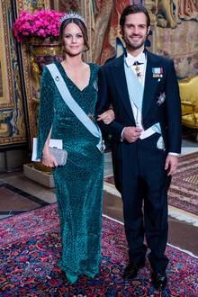 """Beim offiziellen Dinner (auf schwedisch: Representationsmiddag) im königlichen Palast in Stockholm, erscheinenPrinz Carl Philip undPrinzessin Sofia in feierlicher Abendgarderobe. Die hübsche 34-Jährige zeigt sichin einem bodenlangen Samtkleid mit Leoparden-Muster und Cape-Schnitt des schwedischen Labels """"By Malina"""". Dazu trägt sie eine funkelnde Tiara und eine Clutch mit Glitzerapplikationen. Die Kombination aus Samt und Strass sowie dem dezenten Leo-Muster des Kleids ist Sofia jedenfalls sehr gelungen."""