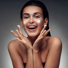 lächelnde Frau die sich Gesichtscreme aufträgt