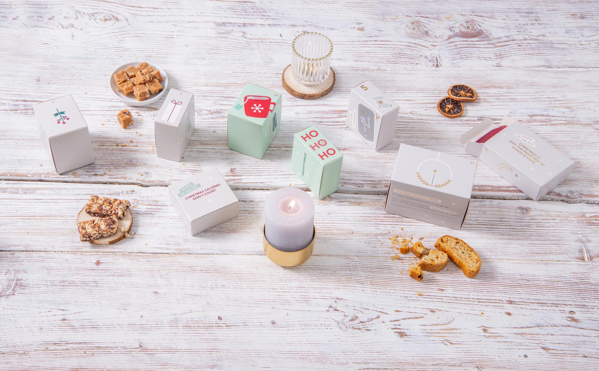 einzelne Päckchen eines Adventskalender, daneben verschiedene Süßigkeiten und zwei kleine Kerzen