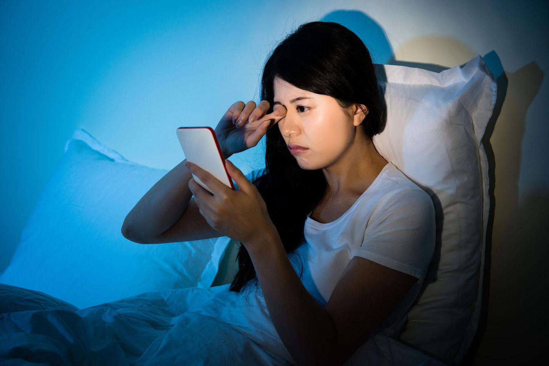 Frau spielt am Smartphone bis sie plötzlich blind ist (Symbolbild)