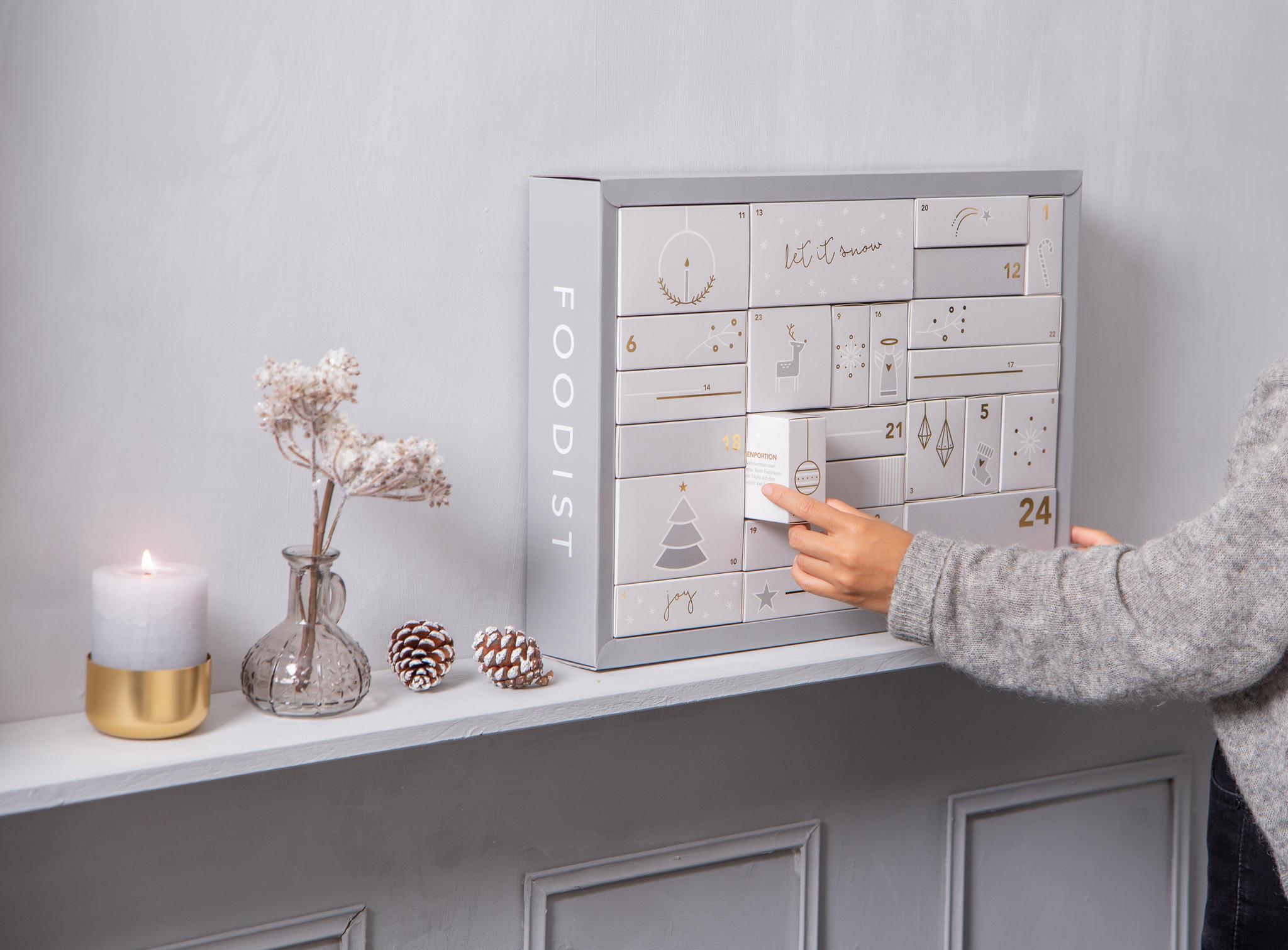 Adventskalender auf einem weißen Regal mit Dekoration, Adventskalender wird geöffnet