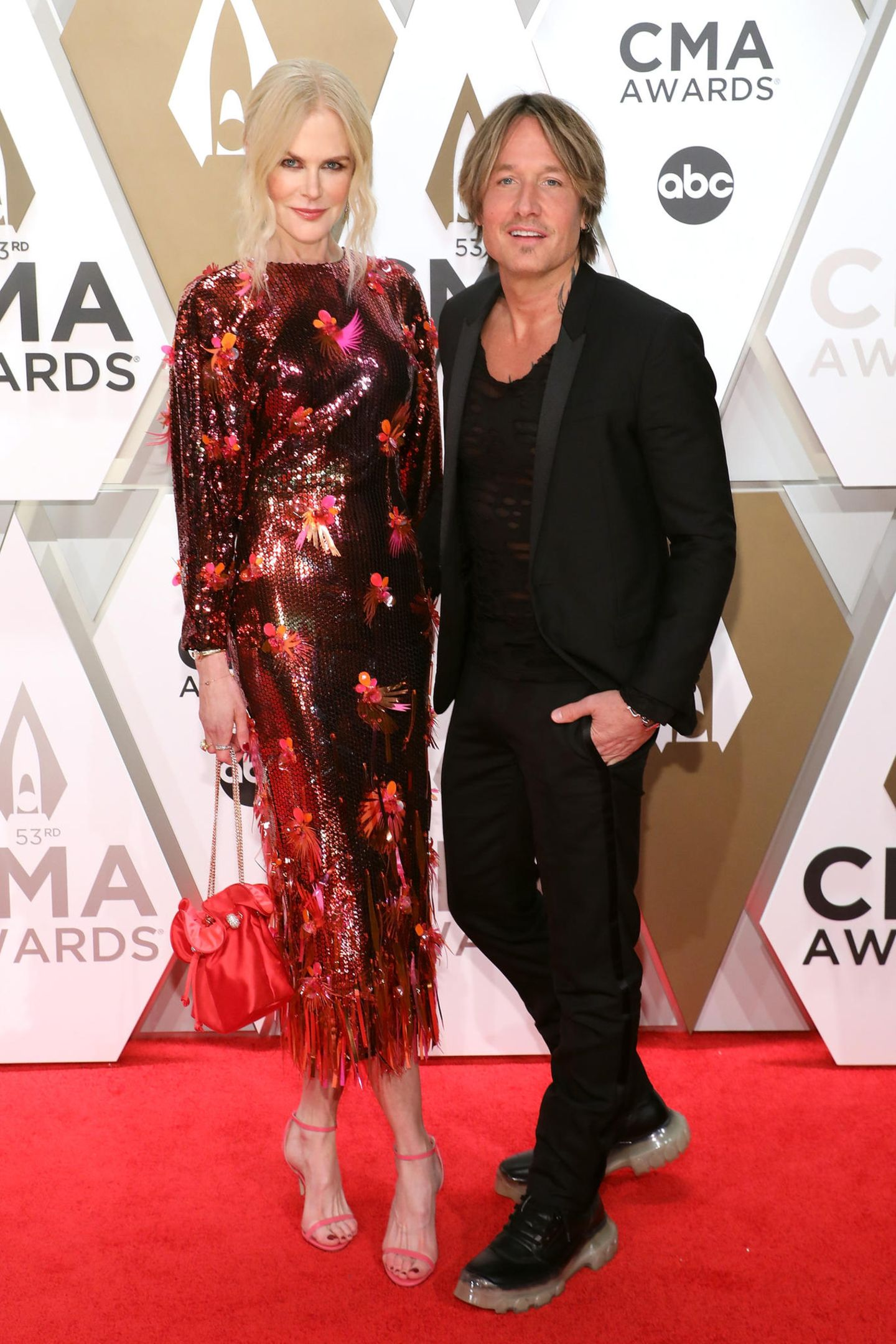 Sänger Keith Urban kam in Begleitung seiner schönen Frau Nicole Kidman, welche sich für ein rotorange schillerndes Paillettenkleid entschied. Die leicht gewellten Haare wurden zum lockern Dutt hochgebunden und eine Satin-Bucket-Bag und zierliche Riemchensandalen rundeten den Look gekonnt ab. Keith Urban hingegen entschied sich für einen schlichteren All-Black-Look und trug ein schwarzes Shirt zum Anzug.