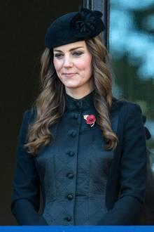 """Herzogin Catherine trägt zu den Feierlichkeiten des """"Remembrance Day"""" im November 2013 diesen schwarzen Mantel von Temperley. Er besticht durch eine strukturierte und glänzende Front, seine perfekte Form und den hohen Kragen. Auf dem Designerstück steckt die Mohnblumen-Brosche der Herzogin, ihr Haar trägt sie offen."""