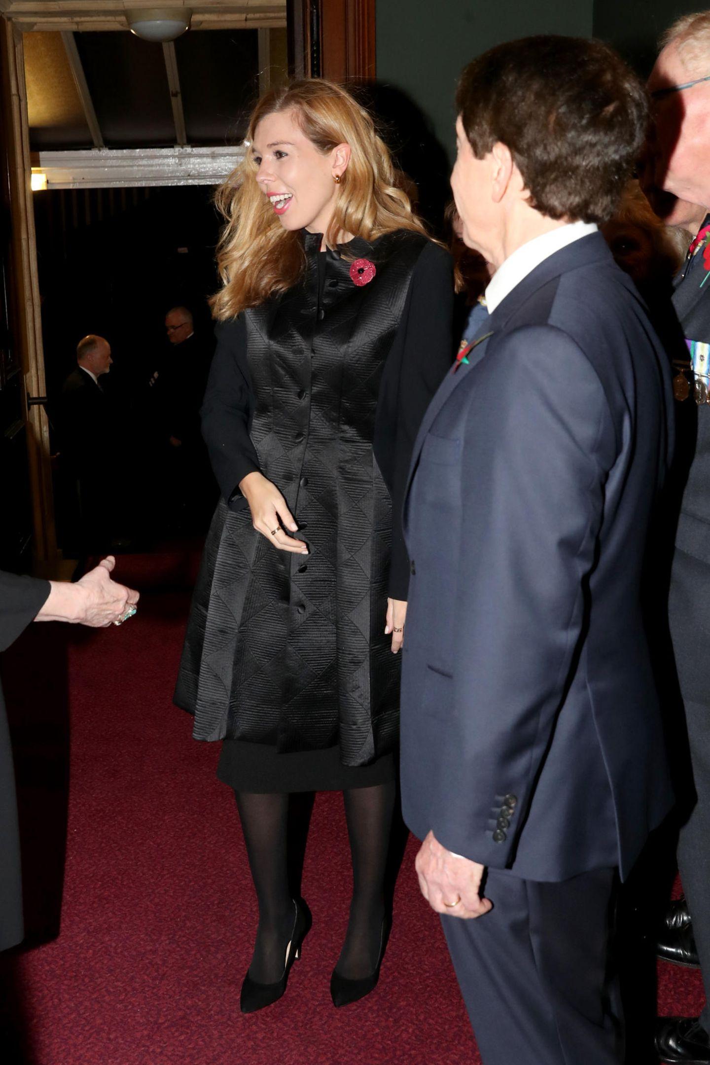 """Carrie Symonds, die Freundin des britischen Premierministers Boris Johnson, wählt genau sechs Jahre später ausgerechnet für einen Auftritt an der Seite der Royals zum """"Festival of Remembrance"""" dasgleichen Mantelkleid. Auch sie trägt ihr Haar offen und in leichten Locken, die Mohnblumenbrosche, die als Symbol des Gedenkens gilt, darf natürlich auch bei ihr nicht fehlen. Ob Herzogin Catherine in der """"Royal Albert Hall"""" zu ihr herüber geschielt und den Look erkannt hat? Zufall kann die Wahl von Carrie eigentlich nicht sein..."""