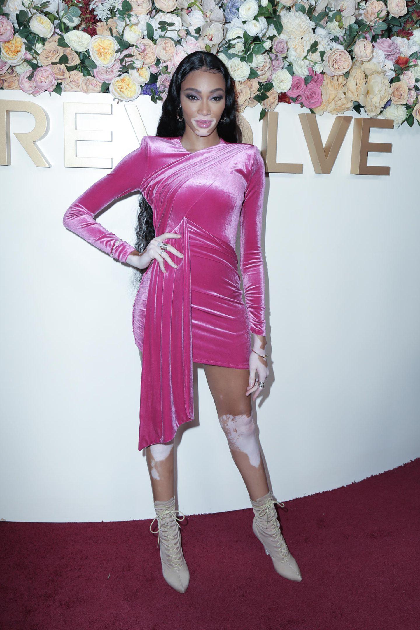 """Supermodel Winnie Harlow erscheint auf den""""Revolve""""-Awards in Hollywood in einem pinkfarbenen Samtkleid in Wickeloptik.Dazu kombiniert das """"Victoria's Secret""""-Modelein Paar beigefarbene Schnürstiefeletten mit hohem Absatz. Funkelnde Kreolen, eingoldener Armreif sowie viele auffällige Ringe perfektionierten den besonderen Look."""