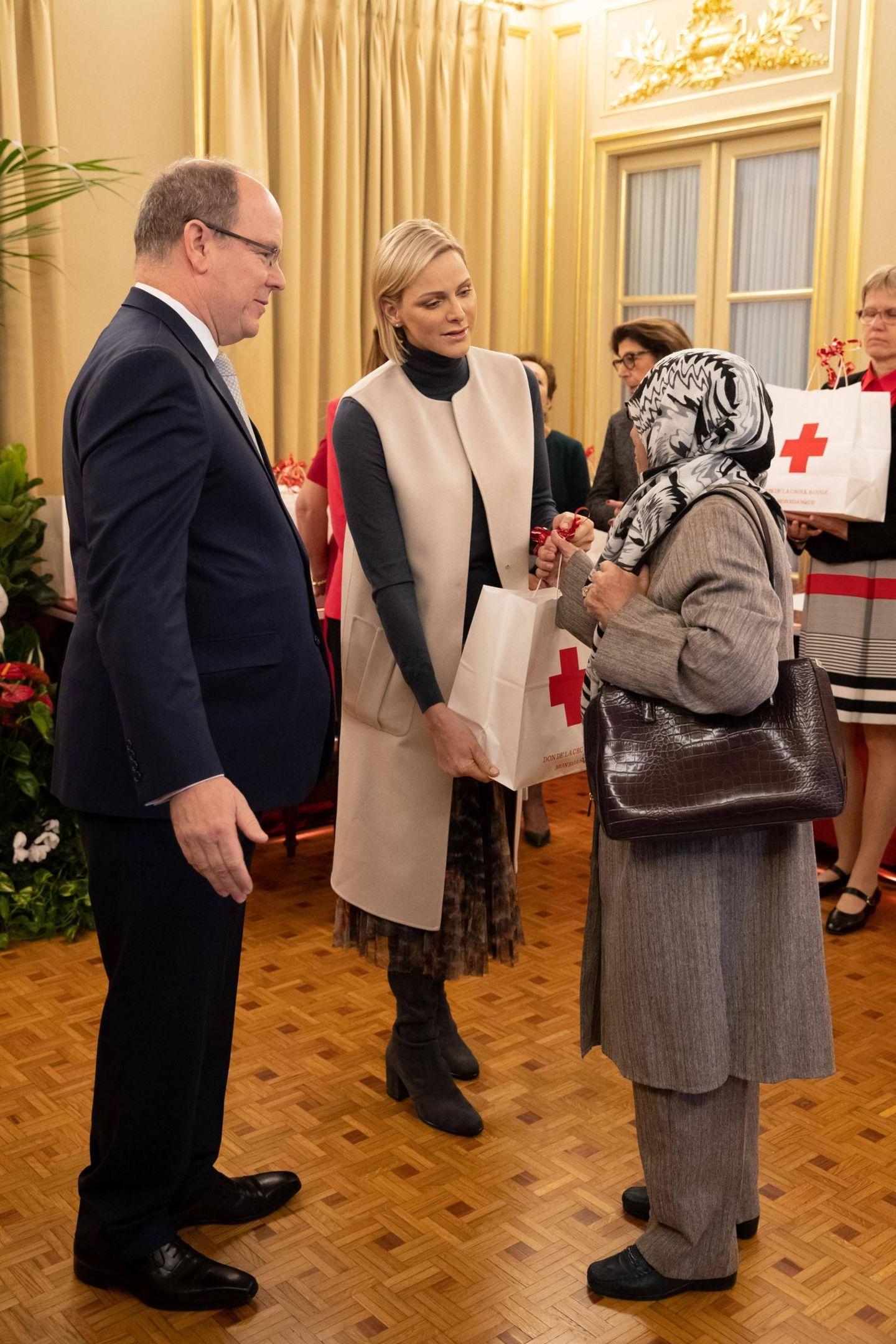 Zusammen mit ihrem Mann, Fürst Albert, verteilt die Mutter von ZwillingenGeschenken an Bedürftige beim Roten Kreuz. Dabei trägt Charlène einen dunklen Rollkragenpullover, einen Midi-Rock und einen auffälligen, hellen Mantel mit breiten Taschen.