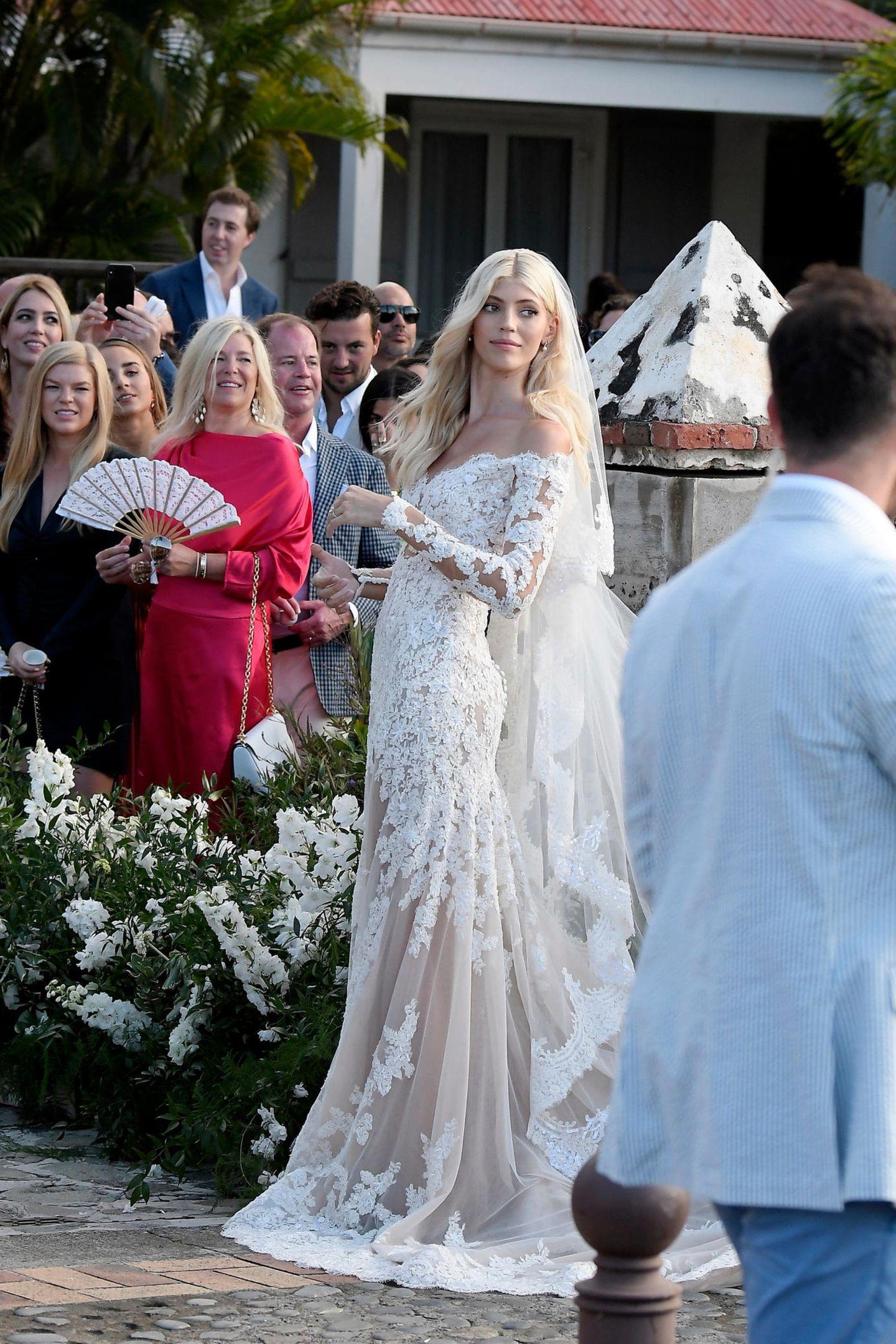 Das Brautkleid des Models besteht komplett aus Spitze, die sich mit transparenten Elementen abwechselt. Das Kleid hat eine leichte A-Linie, wodurch es am Saum glockenartig die Beine der hübschen Blondine umschmeichelt. Der Off-Shoulder-Schnitt gibt den Blick auf Denvons schöne Schultern frei. Für ihren großen Tag wählt das Model ein dezentes Make-up.