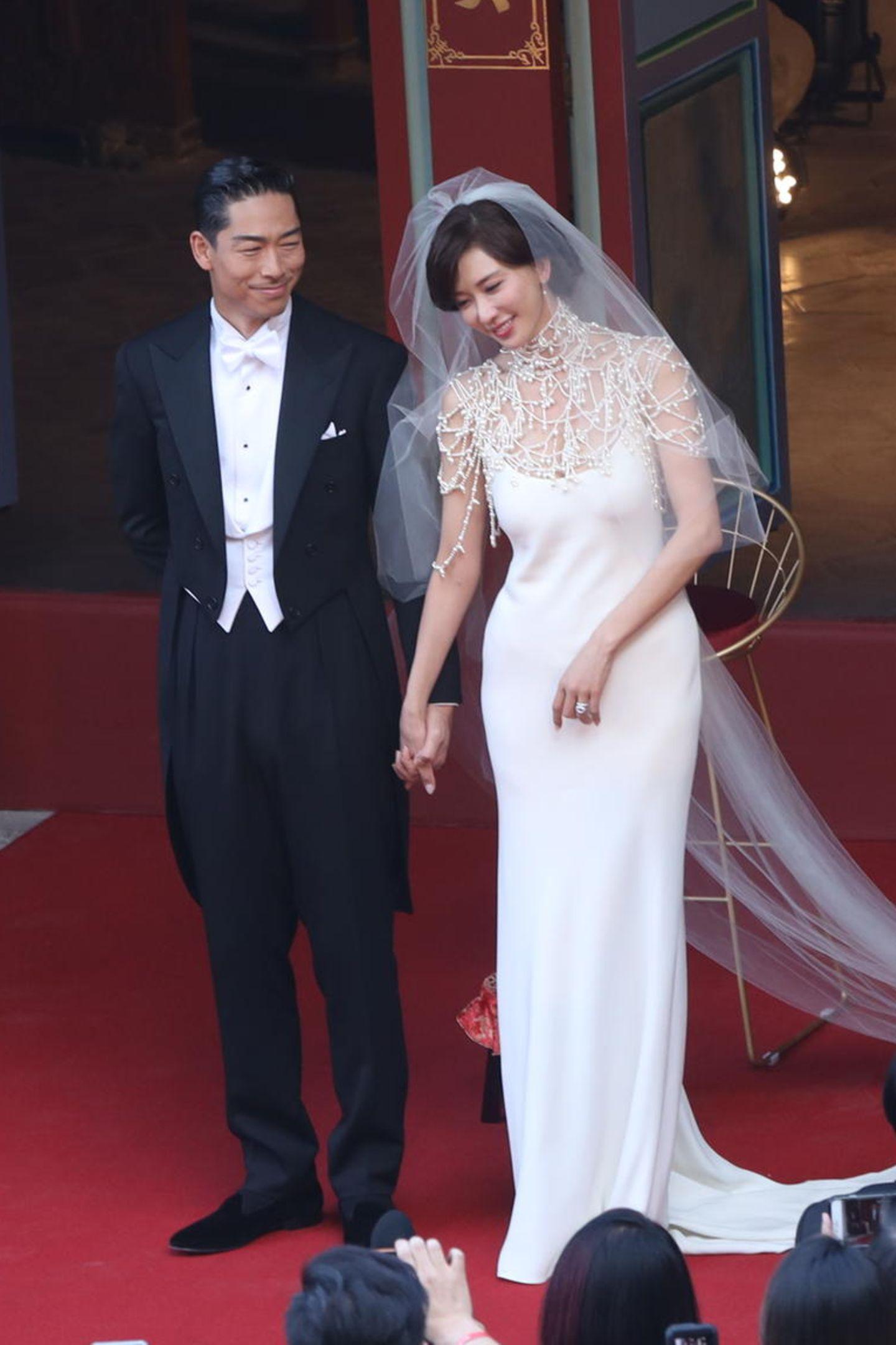Was für eine Traumhochzeit: Das taiwanesische Model Lin Chi-ling hat in einer Mega-Zeremonie den japanischen Boygroup-Star Akira geheiratet. Zur Trauung trugen beide Kreationen aus dem Hause Ralph Lauren. Ihr schlichtes, fließendes Kleid harmoniert perfekt mit dem perlenverzierten Cape.