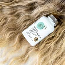 glänzende Haare, auf denen eine Dose mit Haarvitaminen liegt