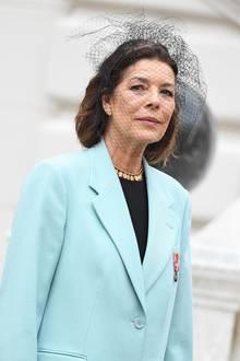 Caroline von Hannover zeigt sich in einem mintblauen Blazer unter dem besonders ihre goldene Kette mit kleinen Anhängern hervorsticht. Dazu trägt sie einen schwarzen Haarreifen mit Netzschleier.