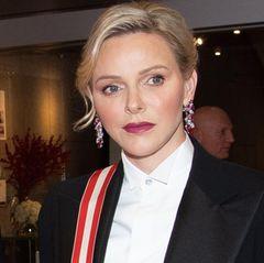 Die Fürstin trägt einen schwarzen Hosenanzug mit einem schlichten weißen Hemd. Die roten Lippen und Hingucker-Ohrringe sorgen für feminine Eleganz.