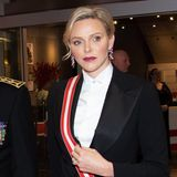Während Fürstin Charlène am Nachmittag ganz in Weiß erschien, setzt sie abends auf eine schicke Zweiteiler-Kombination in Schwarz. Die rot gestreifte Schärpe ist ein toller Akzent auf derweißen, hochgeknöpften Bluse.