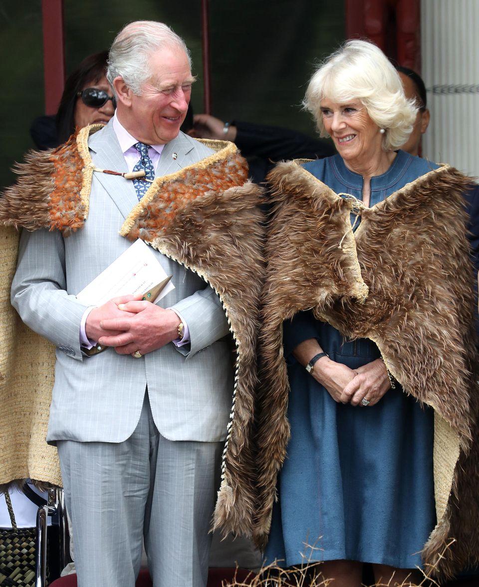 Am vierten Tag ihres Neuseeland-Besuchs hüllen sich Prinz Charles und Herzogin Camilla in die traditionellen Federumhänge der Maori.