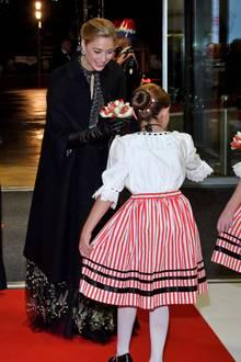 Beatrice, die Ehefrau von Carolines Sohn Pierre Casiraghi, trägt eine schwarze, leicht durchsichtige Robe von Dior und einen schwarzen Mantel und schwarze Lederhandschuhe. Sie wird von zwei traditionell gekleideten Mädchen mit Blumen empfangen.