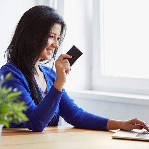 Frau sitzt am Schreibtisch, guckt auf den PC, hat Kreditkarte in der Hand