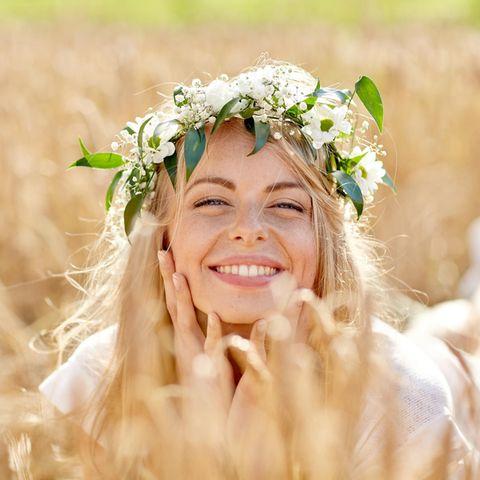 Eine lächelnde, blonde Frau sitzt in einem Getreidefeld und trägt einen Blumenkranz auf dem Kopf
