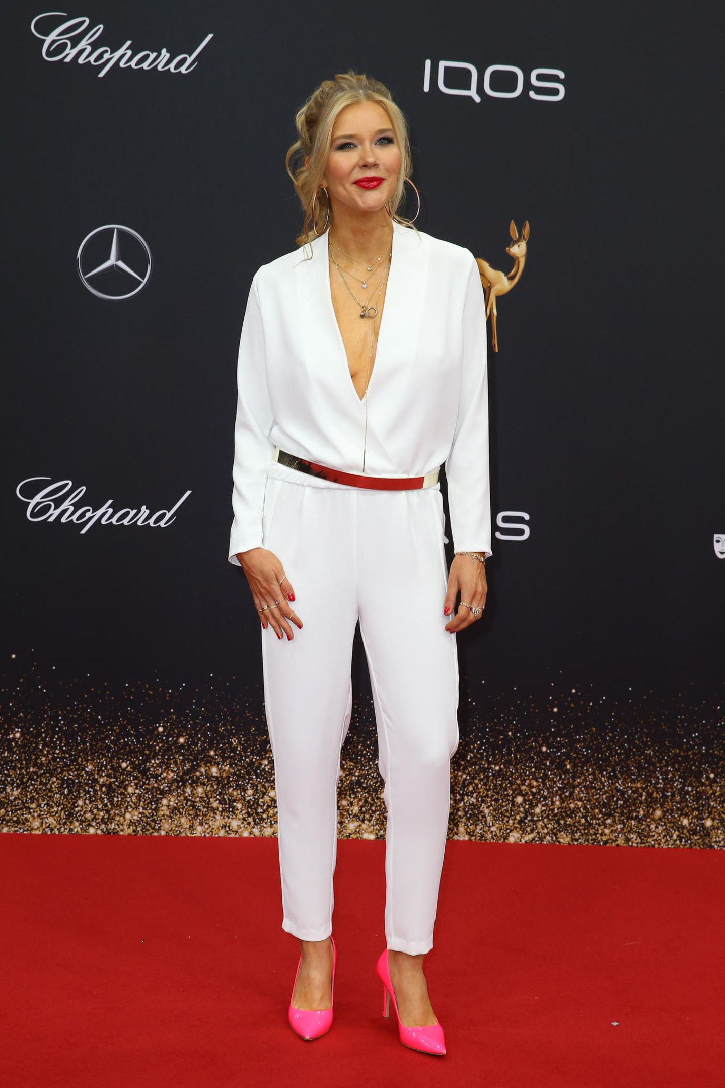 Laura Karasek setzt ihren weißen Jumpsuit mit Gürtel und pinken Pumps in Szene.