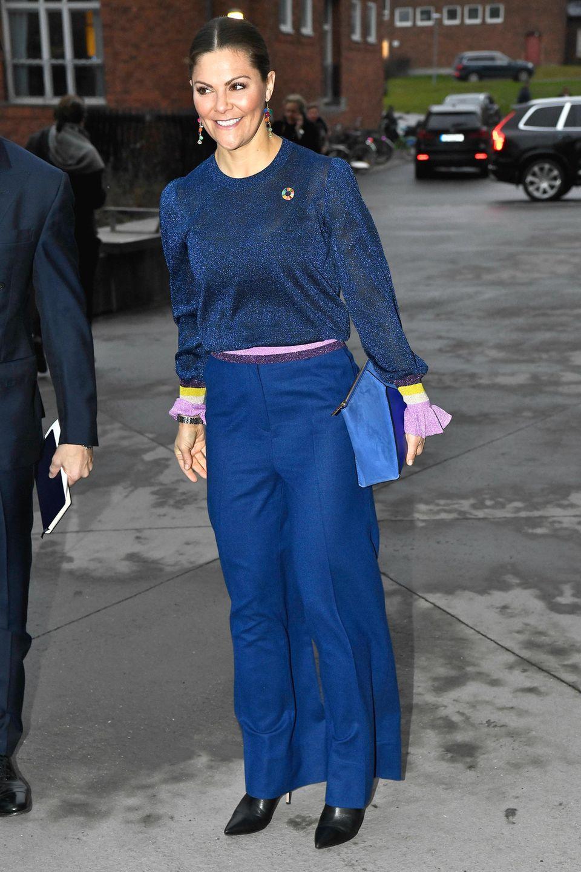 Sogar die Clutch von Kronprinzessin Victoria ist farblich zu ihrem restlichen Outfit abgestimmt. Einziger Farbtupfer stellen ihre langen Ohrringe mit bunten Steinchen dar. Obwohl sich die Blautöne farblich unterscheiden, wirkt ihr Outfit durch die Verwendung mehrerer Materialien stimmig.