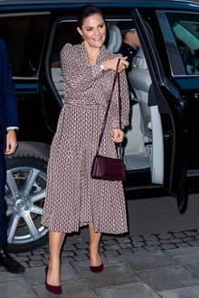 Zu einem Meeting in Stockholm erscheint Kronprinzessin Victoria in einem herbstlichen Outfit. Tasche und Schuhe in dunklem Rot sind perfekt auf das fließende Musterkleid mit Schleife abgestimmt.