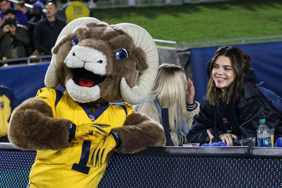 """Gut gelaunt verfolgt Model Kendall Jenner das Football-Spiel der Baltimore Ravens vs Los Angeles Rams und genießt dabei besondere Aufmerksamkeit durch Maskottchen """"Rampage""""."""