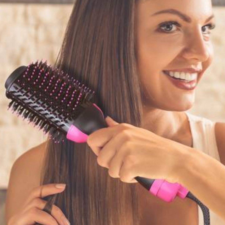 Frau bürstet sich ihre langen Haare mit einer Föhnbürste und lächelt