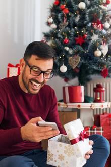 Weihnachtsgeschenke für Männer, Mann packt sein Geschenk aus und freut sich