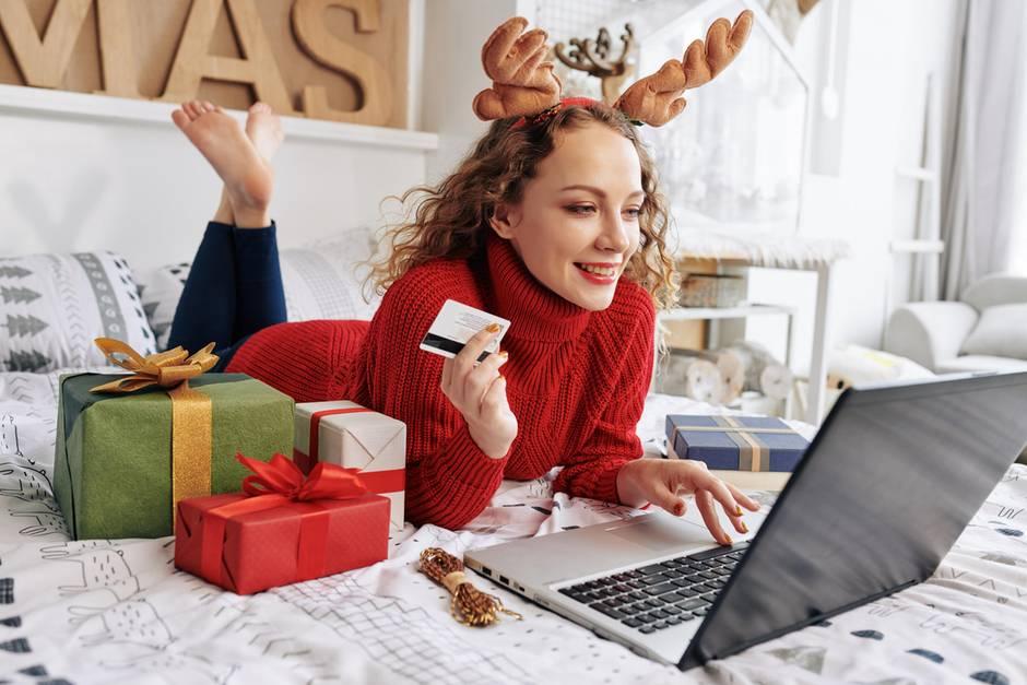 Frau beim Onlineshopping liegt auf Bett mit PC und Geweih auf dem Kopf