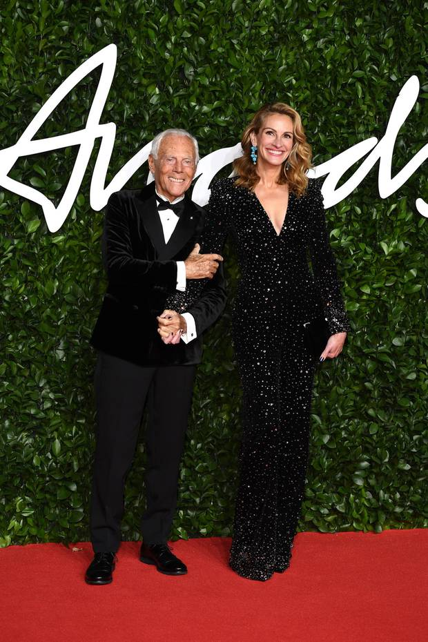 Hollywood-Glamour in London: Eine strahlende Julia Roberts erscheint Hand in Hand mit Designer Giorgio Armani. Sie trägt eine schwarze Glitzerrobe mit tiefem V-Ausschnitt und hat ihr Haar in elegante Wellen gelegt.