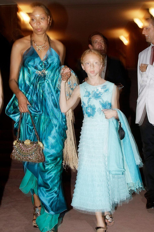 Mit neun Jahren zeigt sich Anna Ermakova zusammen mit ihrer Mutter Angela auf dem roten Teppich der Salzburg Festival Spiele. Sie trägt ein hellblauesKleid mit Rüschen und Blumenapplikationen.