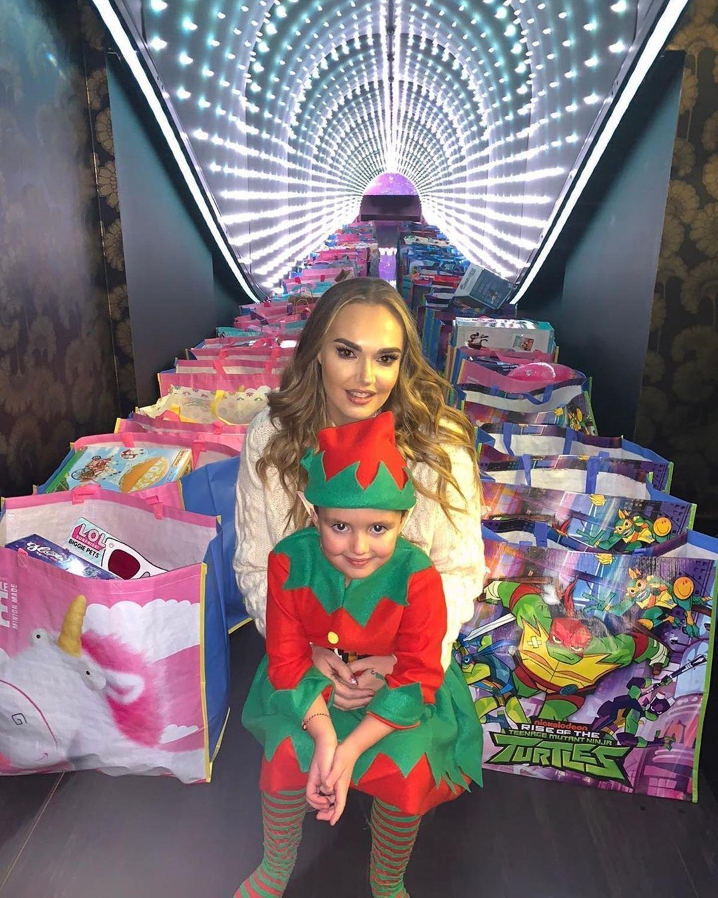 Mitten in einem Meer aus Spielzeugtüten sitzen Tamara Ecclestone und Töchterchen Sophia. Doch all diese Geschenke gehören nicht der 5-Jährigen selbst. Im Gegenteil: Als guter Weihnachtself verkleidet, spendet Sophia sie zusammen mit ihrer Mamaan andere Kinder und macht ihnen damit garantiert eine große Freude!