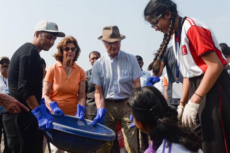 Königin Silvia und König Carl Gustaf von Schweden packen bei ihrem Besuch in Mumbai gemeinsam mit Freiwilligen bei einer Aufräumaktion am Strand tatkräftig mit an.
