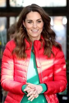 Unter der knallroten gesteppten Jacke trägt sie einen grünen Wollpullover. Ihr brünettes Haar hat sie in leichte Wellen gelegt.