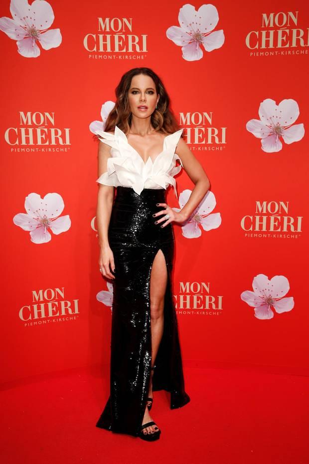 Kate Beckinsale versprüht Hollywood-Glamour in München. Sie trägt eine Haute-Couture-Robe vonYanina Couture und begeistert mit ihrem funkelnden, schwarzen Rock samt hohem Beinschlitz.