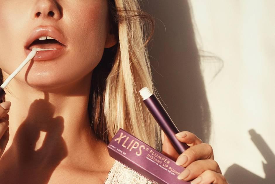 Frau mit vollen Lippen trägt Lippenprodukt auf