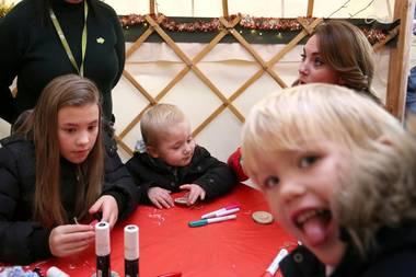 Herzogin wer? Der kleine Freddie, der mit Herzogin Catherine und anderen Kinder und Familien auf derPeterley Manor Farm in Buckinghamshire in der Vorweihnachtszeit bastelt, erlaubt sich mit dem Fotografen einen kleinen Spaß und photobombt dabei den royalen Gast. Catherine nimmt's sicher mit Humor.