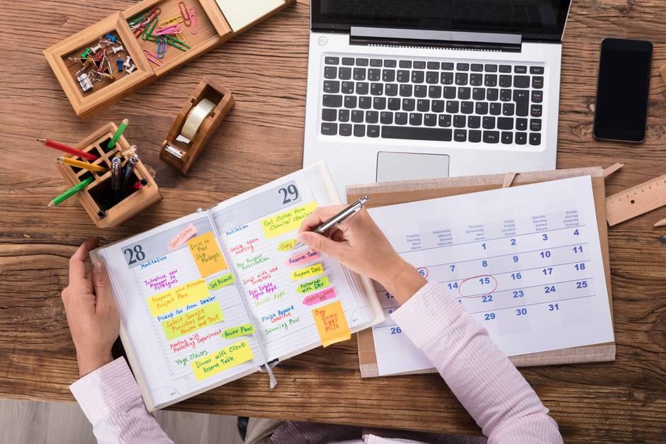 Terminplaner mit Notizen und Post-its, Frau macht Notizen, PC, Schreibtisch, Stifte