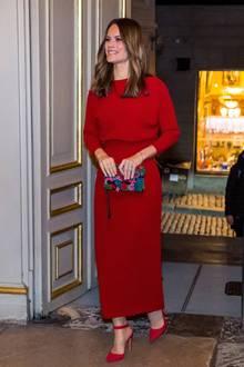 Für ihren Geburtstag entscheidet sich Prinzessin Sofia von Schweden für ein Midi-langes Kleid mit einer figurbetonten Raffung an der Taille und einer 7/8-Länge an denÄrmeln. Spitze, ebenfalls rotfarbene Pumps sowie eine mit Steinchen verzierte Clutch runden den Geburtstagslook der 35-Jährigen gekonnt ab.