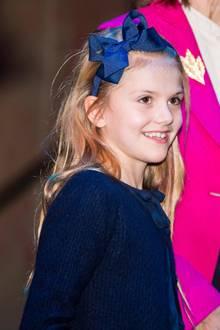 Ihre langen Haare bändigt die kleine Prinzessin mit einem dunkelblauen Haarreif mit einer großen, glänzenden Schleife. Das Accessoire passt nicht nur farblich bestens zum Rest des Outfits, sondern auch stilistisch zur Bluse, die am Kragen ebenfalls mit einer Schleife versehen ist.