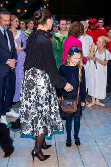Auch in der Schuhwahl sind sich Mutter und Tochter einig: Zu den auffälligen Röcken kombinieren sie farblich passende, elegante Lackschuhe. Anders als Victoria, die spitze Pumps trägt, entscheidet sich Estelle für flache Ballerinas.