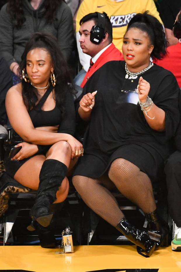 Sängerin Lizzo schaut sich in Los Angeles ein Spiel der Lakers an. In einem schwarzen, von vorne schlicht aussehenden, Kleid, Netzstrumpfhose und schwarzen Lack-Stiefelettennimmt sie auf der Tribüne Platz. Jedoch nur für einen kurzen Moment...