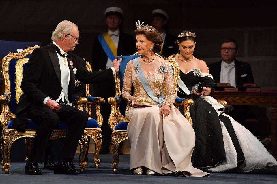 """Royales Trio: König Carl Gustaf nimmt neben seiner Frau Königin Silvia undKronprinzessin Victoriabei der Verleihung der Nobelpreise 2019 im Konzerthaus in Stockholm Platz. Den Dresscode """"Herren in dunklen Anzügen und Krawatte,die Damen in einem Kleid"""" haben die schwedischen Royalssouverän erfüllt."""