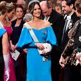 Prinzessin Sofia sieht in ihrer himmelblauen Robe mit Carmen-Ausschnitt zauberhaft aus. Die Tulpenärmel betonen ihre schmale Taille. Zu dem Look kombiniert Sofia eine weiße Clutch.