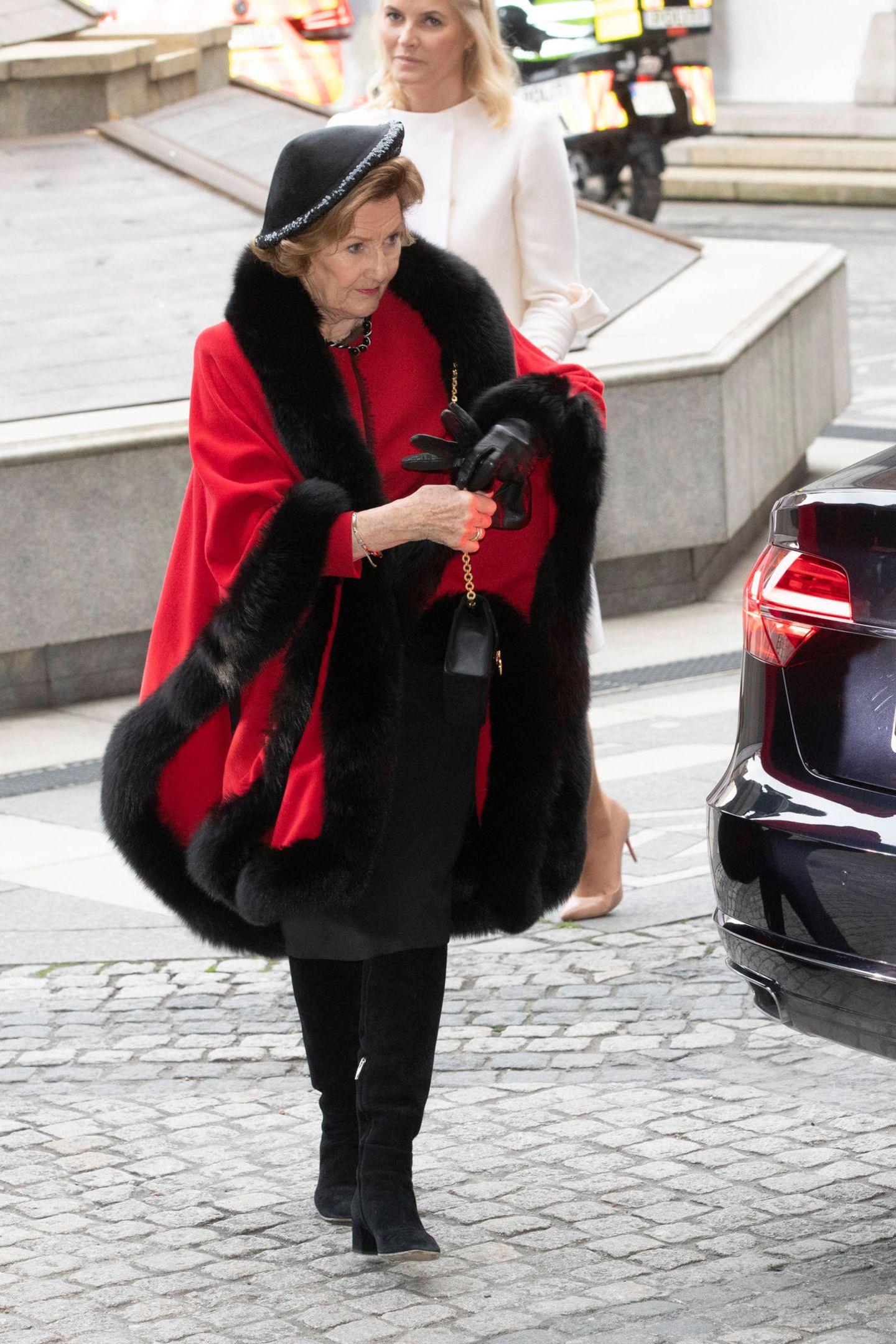 Königin Sonja trägt bei ihrer Ankunft im Rathaus von Oslo einen roten Mantel mit Pelzbesatz und Hut.