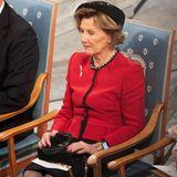 Statt eines Kleids trägt die Königin Weste und Rock und kombiniert dazu schwarze, kniehohe Stiefel. Statt auf eine traditionelle Armbanduhr scheint sie auf eine Smart Watch zu setzen.