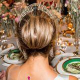 Die kunstvoll hochgesteckten Haare der Dreifach-Mama legen den Blick auf die runden pinken Knöpfe frei, die den durchsichtigen Stoff ihres Kleides hinten zusammenhalten.