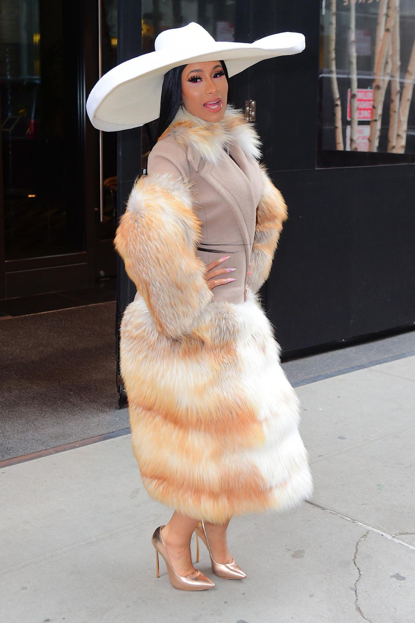 """Für diesen Look erntet Cardi B harte Kritik! """"Unglaublich, dafür lösche ich dich aus meinem Instagram-Feed!"""", lautet ein Kommentar einer erbosten Userin auf Instagram. Nach Kunstfell sieht das wirklich nicht aus. Mal ganz davon abgesehen, dass der Mantel mit den unvorteilhaften Proportionen echt schräg aussieht, sollte die Sängerin mit 42 Millionen Instagram-Followern ihre Vorbildfunktion ernst nehmen und die Fellindustrie nicht unterstützen."""