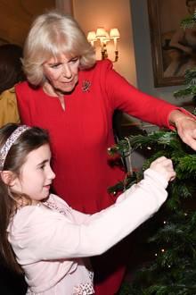 Herzogin Camilla hängt mit einem Mädchen Weihnachtsdeko auf